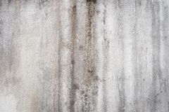 Water damage causing mold growth on the interior walls of a property. Cracked concrete wall covered with gray cement surface as background royalty free stock photography