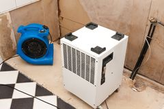 Water damage restoration. Elimination of water damage with fan and dryer royalty free stock images