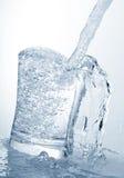 Water dat een glas tegenkomt Stock Afbeelding