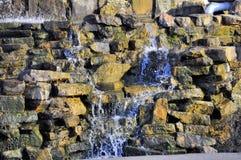 Water dat onderaan rotsen stroomt Stock Fotografie