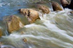 Water dat over rotsen meesleept Stock Afbeeldingen
