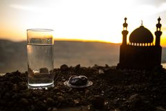Water and dates. Iftar is the evening meal. View of decoration Ramadan Kareem holiday on sand. Festive greeting card, invitation. For Muslim holiday. Selective stock photos