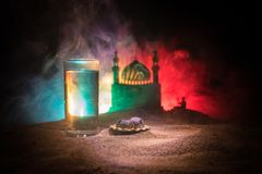 Water and dates. Iftar is the evening meal. View of decoration Ramadan Kareem holiday on sand. Festive greeting card, invitation. For Muslim holiday. Selective stock images