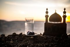 Water and dates. Iftar is the evening meal. View of decoration Ramadan Kareem holiday on sand. Festive greeting card, invitation. For Muslim holiday. Selective royalty free stock image