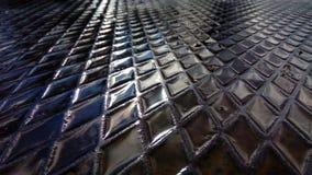 Water in de cellen van een geweven metaalplaat De straten van de moderne stad na de regen stock afbeelding