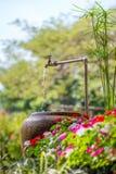 Water in de steenkruik in de tuin Stock Afbeeldingen