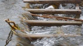 Water in de stroomstromen door een houten hindernis stock footage