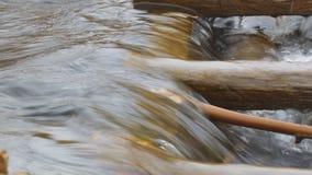 Water in de stroomstromen door een houten hindernis stock videobeelden