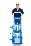 Water Delivery on Hand Truck. Delivery man with fifteen gallons of drinking water on a hand truck.  Full body isolated on white Stock Image