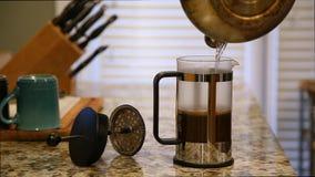 Water die in een Franse pers op een keuken tegenbovenkant worden gegoten met koffie het brouwen en multi gekleurde koffiemokken stock videobeelden