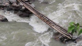 Water die in een Himalayan-rivier onder een kleine houten brug, Nepal meeslepen stock video