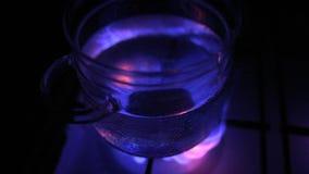 Water die in glaspot bij gasfornuis koken stock videobeelden