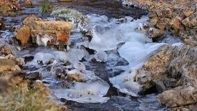 Water die onderaan een rotsachtige, ijzige kreek stromen stock video