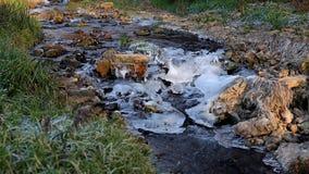 Water die onderaan een rotsachtige, ijzige kreek stromen stock videobeelden