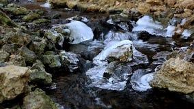 Water die onderaan een rotsachtige, ijzige kreek stromen stock footage