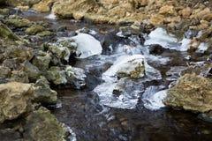 Water die onderaan een rotsachtige kreek door ijs vloeien stock foto