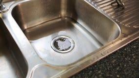 Water die onderaan het afvoerkanaal in keukengootsteen stromen stock videobeelden