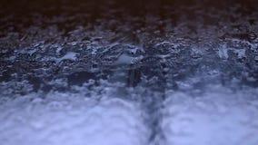 Water die op autoglas druipen op vage achtergrond