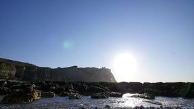 Water die over de rotsen op de achtergrond van bergen en zonnige hemel stromen stock footage