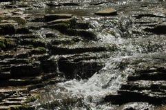 Water die over rotsen stromen Stock Afbeelding