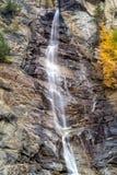 Water die over rotsen, waterval en de herfstkleuren in de bergen, de gele en rode bomen draperen Stock Foto's