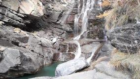 Water die over rotsen, waterval en de herfstkleuren in de bergen, de gele en rode bomen draperen stock footage