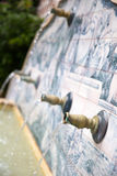 Water die uit pijpen in een fontein komen Stock Fotografie