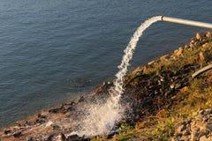 Water die van een drainagepijp in de rivier stromen Royalty-vrije Stock Foto's