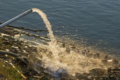 Water die van een drainagepijp in de rivier stromen Stock Afbeeldingen