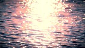 Water die in zonlicht met zonweg schitteren op purper en blauw water stock videobeelden