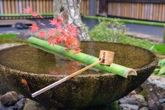 Water dipper on stone basin with autumn leaf. Water dipper on green bamboo wood at stone basin with red maple leaves at Enkoji Temple in Kyoto, Japan Stock Image