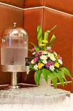 Water dispenser with glasses and flower vase at reception Stock Images
