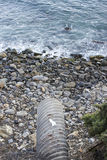 Water Drain Leads to Rocky Ocean Beach. A water drain leads to rocky ocean beach below Stock Photo