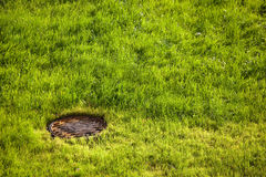 Water drain metal rusty hatch on green grass field. Water drain drainpipe system royalty free stock photo