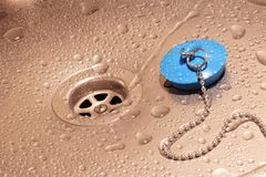Water drain, drops on the sink and drain plug. royalty free stock photos
