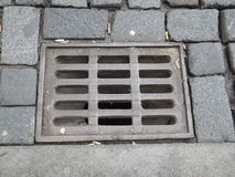 Water drainage hole with grid on a cobbled street. A water drainage hole with grid on a cobbled street Royalty Free Stock Images