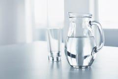 Water dranken Glas en Waterkruik met Water Saldo, Hydratatio stock foto's