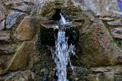 Water for drinking flows from old stones close up royalty free stock image