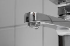 Water dripping from a faucet. On the background tiles stock images