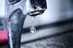 Water Dripping from Tap. Macro shot of a water drop in the Kitchen sink Royalty Free Stock Photo