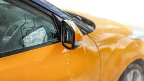 Water dripping from wet side mirror of yellow car washed in carwash stock photography