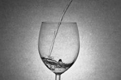 Water dripping into wine glass stock image