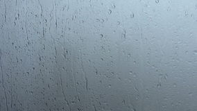 Water drips on a window glass. Background shot of rainy water drips on a window glass stock video