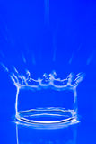 Water Drop. A drop of water splashing into water, on blue background stock photo