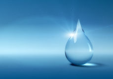 Water drop. Glowing water drop with copyspace on blue background. Fine noise effect Royalty Free Stock Image