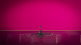 Water drop. Extreme close-up of water drop at high speed with pink background and reflection Royalty Free Stock Image