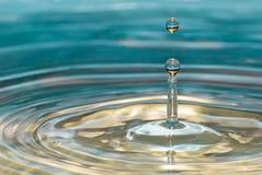 Water drop above water pillar Stock Photos