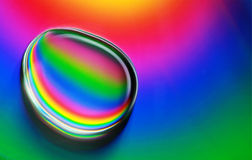 Water drop abstract background. A close up photo of a water drop on a cd with a rainbow background Stock Image
