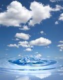 Water drop against blue sky. Water drop splashing in clean water against blue sky Royalty Free Stock Image
