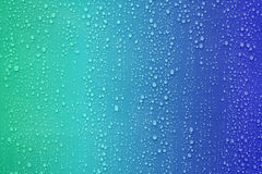 Water drop on blue color gradient background. Stock Photo